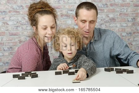 happy family mother father and child playing dominos
