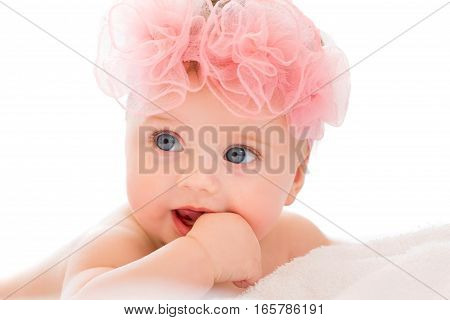 Cute little baby girl with big blue eyes wearing a pink bow.