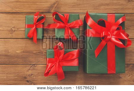 Lots of Gift boxes on wood background. Presents decorated with red ribbon bows. Christmas and other holidays concept.