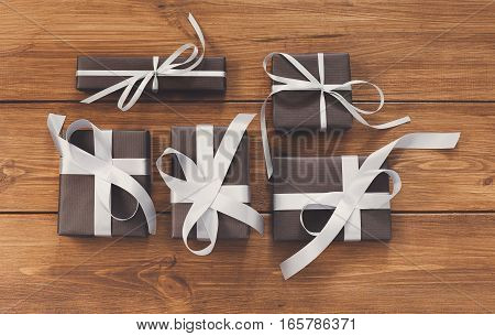 Lots of Gift boxes on wood background. Presents decorated with white ribbon bows. Christmas and other holidays concept.