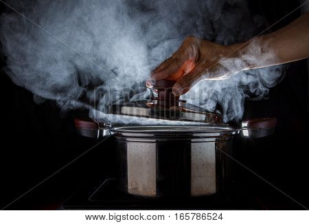 close up hand open hot steam pot