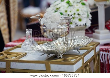 Church supplies for baptism on the table. Ceremony of a christening in church. Interior Of Orthodox Church
