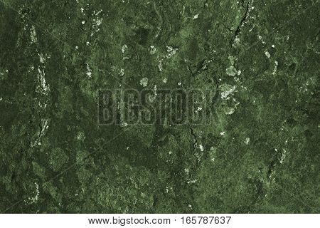 Unique abstract mossy dark green stone surface. Its color resembles moss and the structure is like a wall, lichen, topographic map or landscape from above. The texture is dry and rough.
