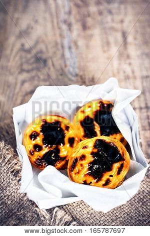 Pastel de Nata - creamy egg tart with sweet curstard black crust and sugar powder on wooden background. Pasteis de Belem pastry