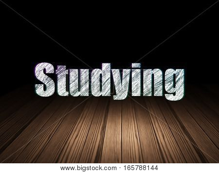 Studying concept: Glowing text Studying in grunge dark room with Wooden Floor, black background