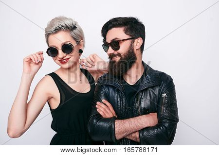 fashion beautiful couple in black clothes wearing trendy glasses and posing over white background. Hipster young bearded man and trendy blond woman.