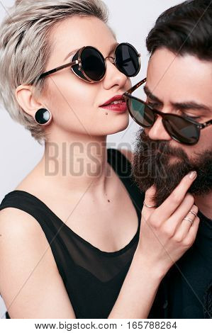 Close up of passionate young people in love wearing black clothes and stylish sunglasses. Closeup portrait of modern young woman embracing hipster bearded man