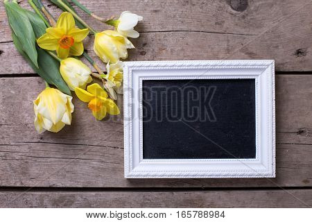 Fresh yellow daffodils and tulips flowers and empty blackboard on vintage wooden background. Selective focus. Place for text.