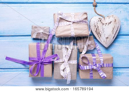 Many festive gift boxes with presents and decorative heart on blue wooden background. Selective focus. Flat lay. Top view.