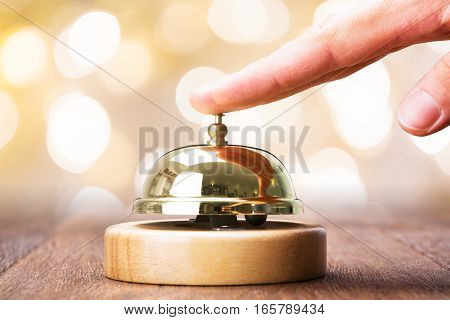 Close-up Of Person Ringing Service Bell On Wooden Desk