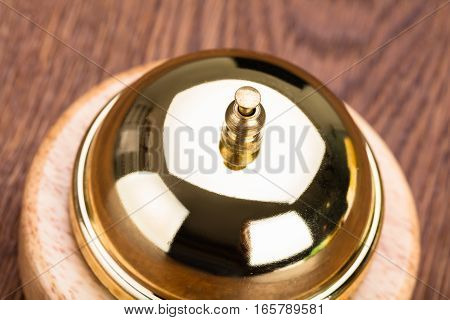 High Angle View Of Service Bell On Wooden Desk In Hotel