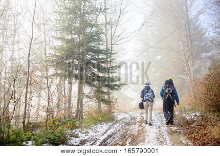 Man And Woman Backpackers Hiking On Foggy Forest Mountain Trail