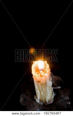 Candle ignited with the wax falling down in a chandelier isolated in black