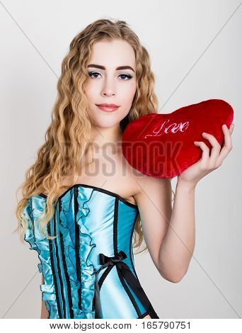 Young and beautiful curly girl in blue corset holding a red heart pillow.