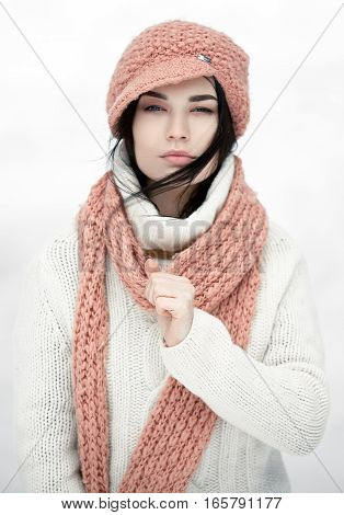 Portrait of girl in sweater hat and scarf. Scarf wrapped around her neck. Against white background.
