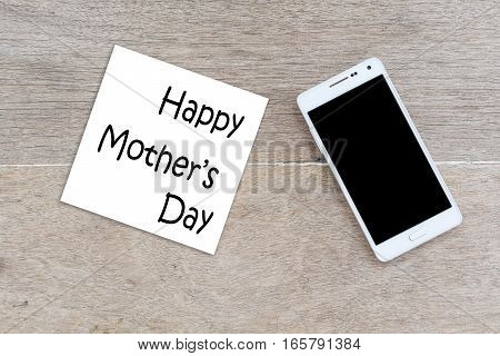 Happy Mother's Day inscription with mobile phone wooden background.