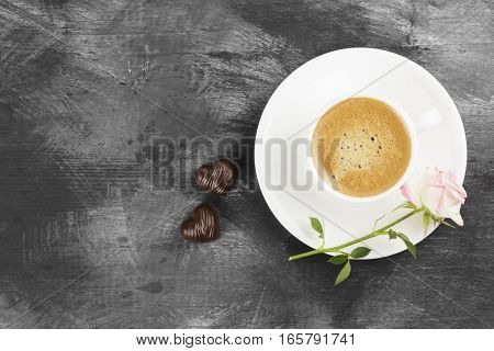 Espresso coffee in a white cup a pink rose and chocolates on a dark background. Top view copy space. Food background.