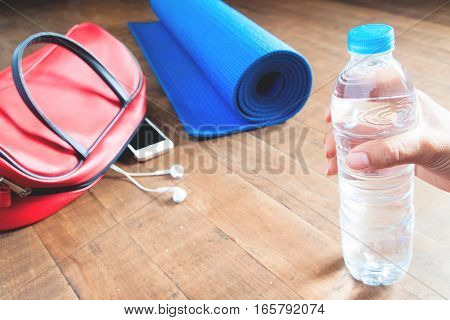 Woman hand holding bottle of water with yogamat baf and phone background