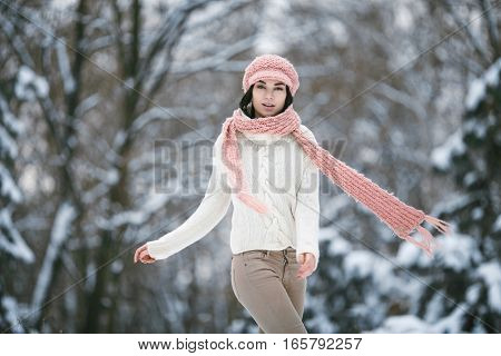 Girl in sweater scarf and hat in winter forest. She wrapped herself in sweater and scarf.