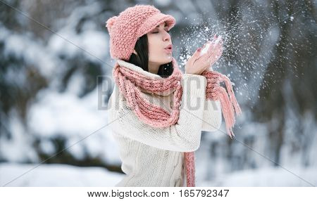 Girl in sweater scarf and hat in winter forest. She wrapped herself in sweater and scarf. She is holding snow and blowing on snowflakes. Snowflakes fly apart.