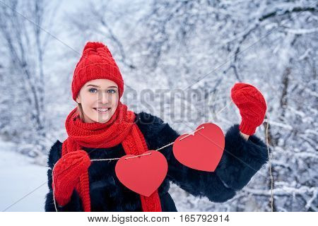 Love and valentines day concept. Smiling woman holding garland of two red paper hearts shape - blank copy space for letters or text, looking at camera over winter landscape