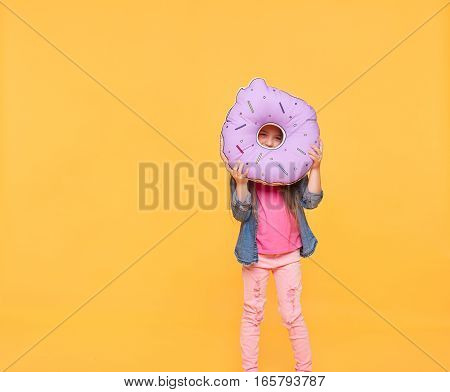 girl looking through a big violet donut over yellow background. Little kid holding a number zero with copy space. Null numeral