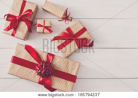 Top view of Gift boxes on white wood background. Presents in craft paper decorated with red ribbon bows. Birthday, valentine and other holidays concept, copy space