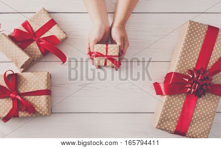 Top view of Gift boxes in hands on white wood background. Presents in craft paper decorated with red ribbon bows. Birthday, valentine and other holidays concept.