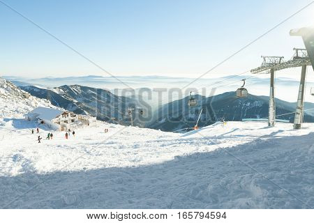 Cable Car Cabins Going Up And Down High In The Mountains At A Winter Sports Resort Area On A Sunny D