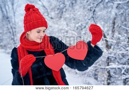Love and valentines day concept. Smiling woman holding garland of two red paper hearts shape - blank copy space for letters or text, looking down at hearts over winter landscape