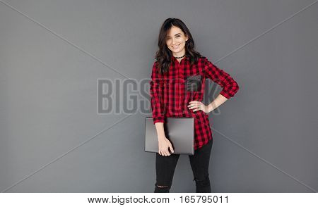 Young student girl smiling and holding a laptop computer while standing over a grey background. Brunette Woman in casual checked shirt with copy space for text