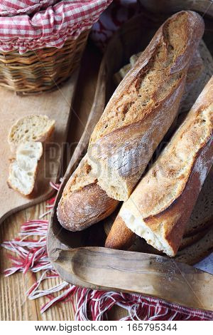 Traditional French country bread in wooden tray. Top view