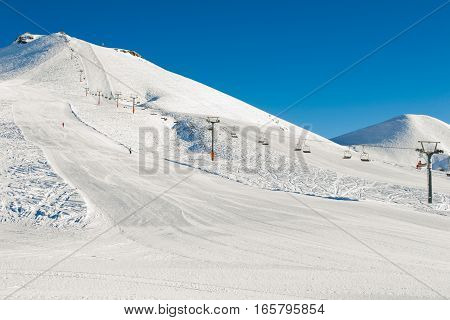 Photo of the Winter mountains background with ski slopes and ski lifts. Skiing resort. Extreme sport. Active holiday. Free time concept.