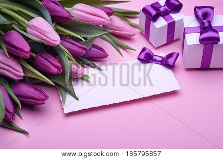 Greeting card, a bouquet of spring tulips, gifts in a beautiful package, bow from satin ribbon, a few boxes with gifts, the gift set on a pink background
