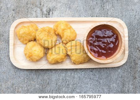 Chicken nuggets with tomato sauce on wood tray