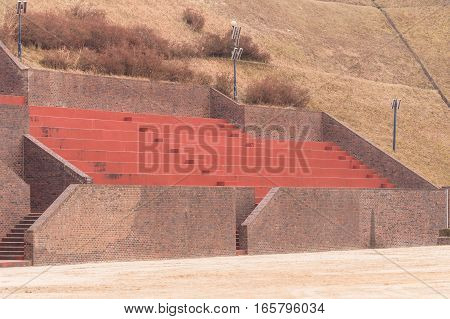 Bleachers at a football field made of red brick and concrete built on the side of a hill