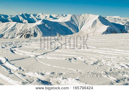 Photo of the Freeride concept. Ski trail on snow. Greater Caucasus Mountain Range in Georgia on background. Negative space for text. Extreme sport. Active holiday.