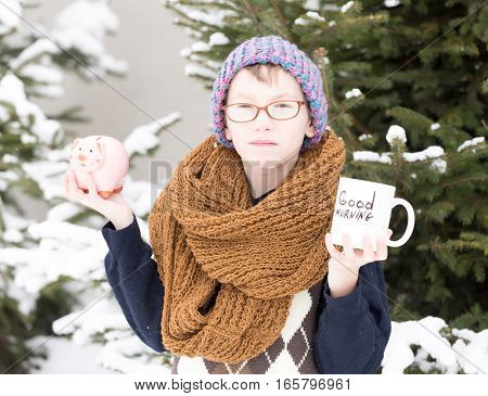 small boy or cute nerd kid in glasses hat sweater and fashionable knitted scarf holds cup with good morning text and pig moneybox in winter outdoor at green fir tree with snow on natural background