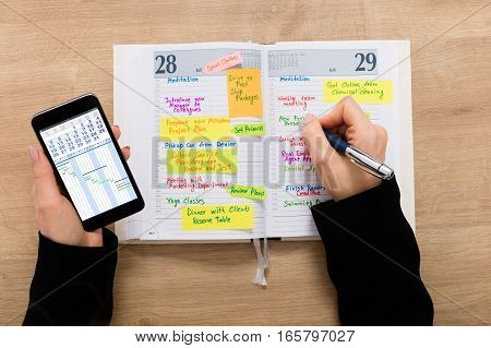High Angle View Of A Businesswoman Writing Schedule In Diary Using Mobilephone On Wooden Desk