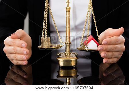 Female Lawyer Protecting Justice Scale With Coins And House Model At Table
