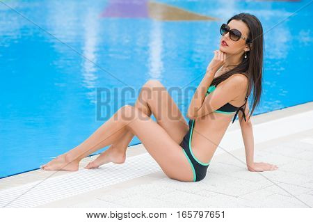 beautiful woman resting by the pool. sunbathing on the loungers by the pool