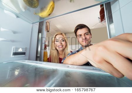 Young Happy Woman Looking At Male Worker Repairing Inside The Refrigerator