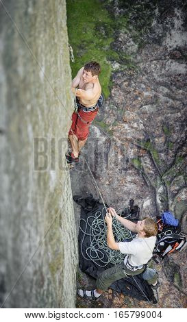 Muscular Rock Climber Climbs On Overhanging Cliff