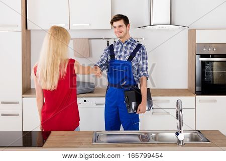 Smiling Housewife Woman Shaking Hands With Male Plumber After Fix In The Kitchen