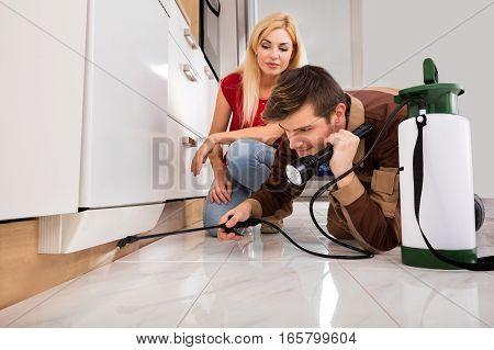 Woman Looking At Exterminator Worker Spraying Insecticide Chemical For Termite Pest Control In House Kitchen