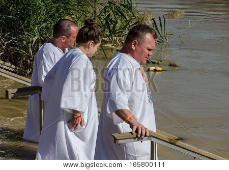 Religious Christians Immerse Themselves Into The Waters Of The Jordan River. Israel Side