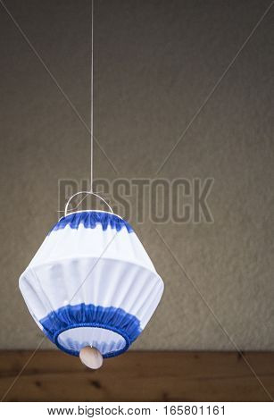 Hanging self made lamp in front of a wall