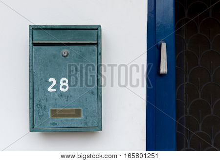 Old green metal letter box and house number on an a white wall.