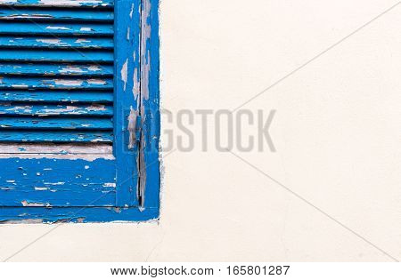 Blue closed old stained wooden window on a white wall.