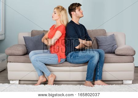 Young Sad Couple In Fight With Arms Crossed Sitting On Sofa After Quarrel At Home